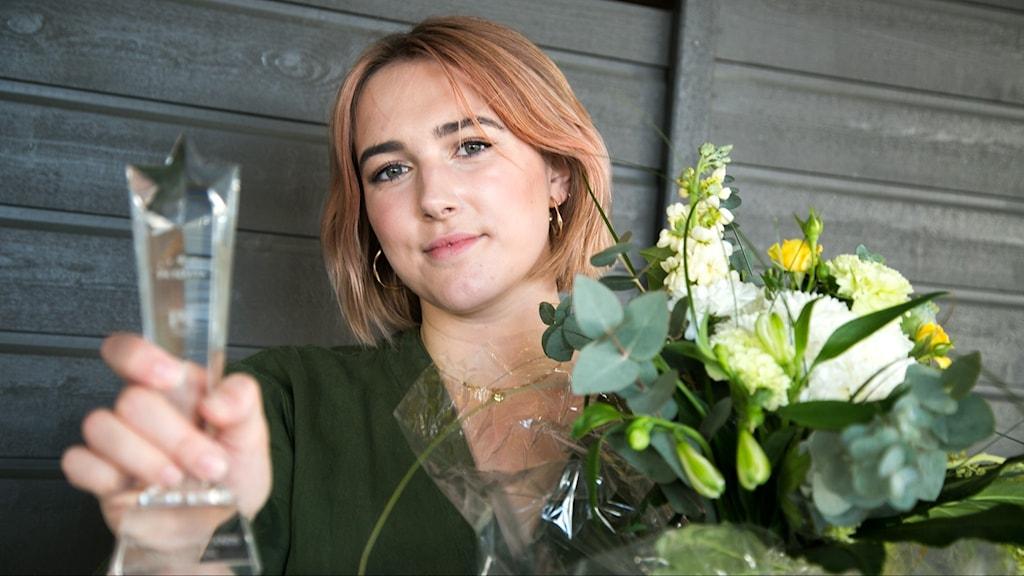 Artisten Nina Bring står mot en mörk vägg och håller i en blombukett och en pokal i genomskinligt glas.