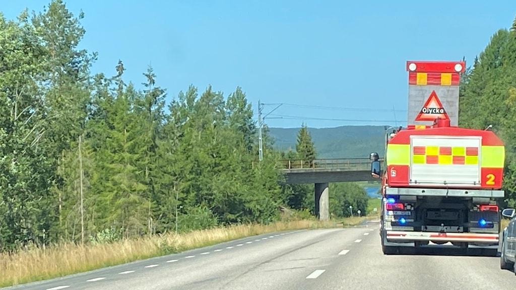 Räddningsfordon står på en väg, till höger bakom står en personbil. Lite längre fram på vägen är det en bro.