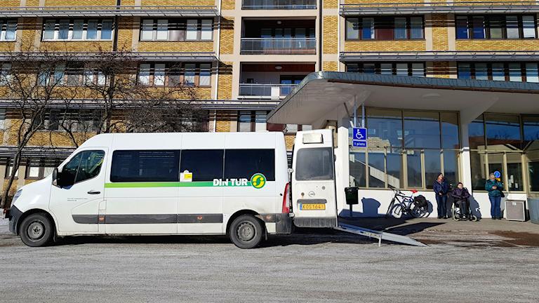 En vit, handikappanpassad buss står med rullstolsrampen utfälld vid entrén till Sollefteå sjukhus.
