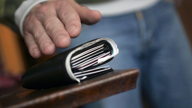 Hand som är på väg att ta en plånbok som ligger på ett bord.