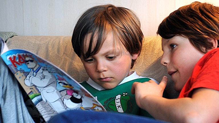Två bröder läser en serietidning tillsammans. Foto: Hasse Holmberg/TT