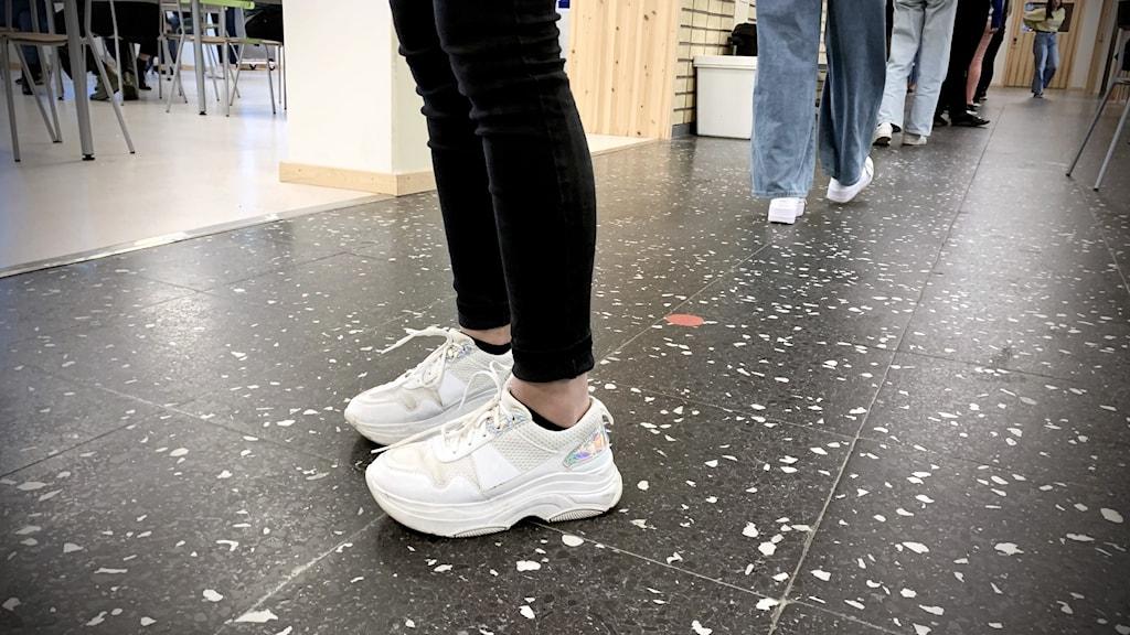 En elev står i skolkorridor. Bara benen och fötterna syns. Svarta jeans och vita sneakers.