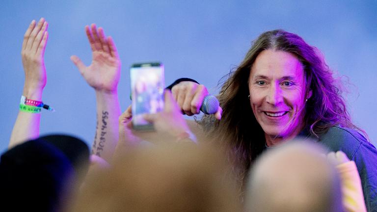 E-type håller ut mikrofonen över publiken under en konsert på Bråvalla festival 2016. Foto: Izabelle Nordfjell/TT