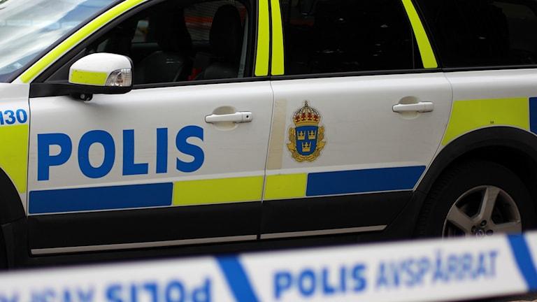 Polisbil med avspärrningsband i förgrunden. Foto: Ann-Charlotte Carlsson/Sveriges Radio