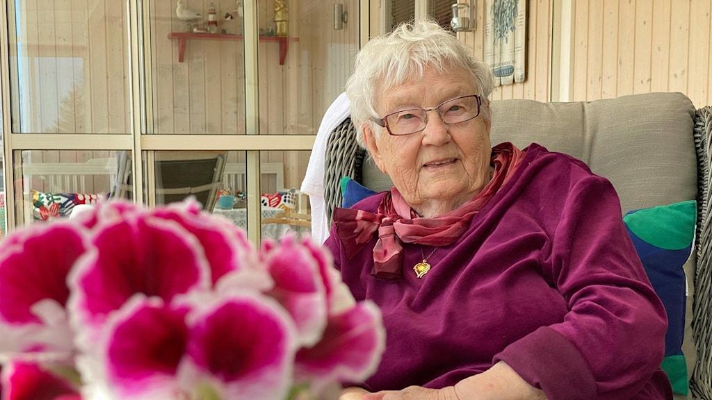 Ines Lidström sitter i en lila glansig tröja och en matchande sjal och ler mot kameran. Framför henne står en cerise blombukett.