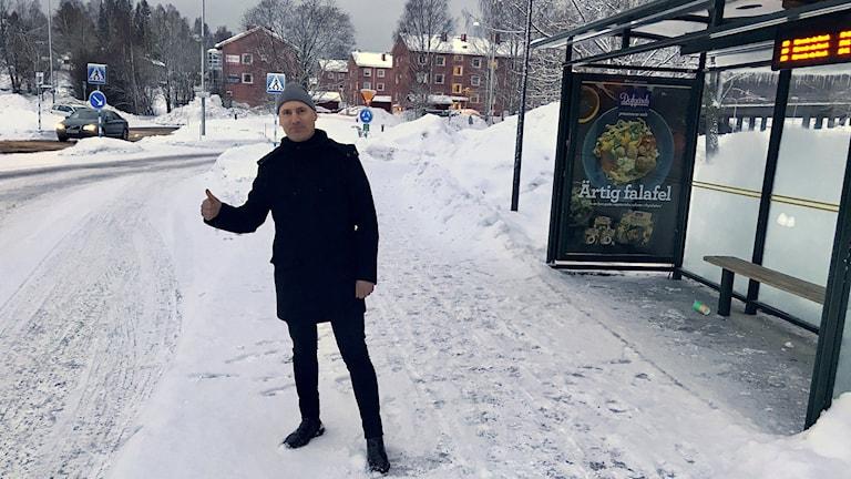 Kommunchef Andreaz Strömgren på Timrå kommun står och liftar vid en busshållplats. Foto: Lotte Nord/Sveriges Radio