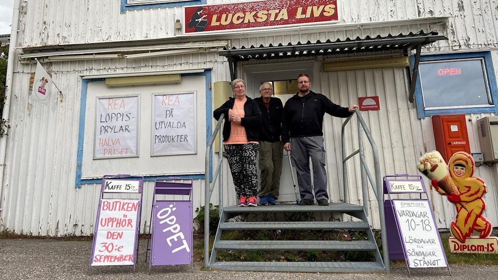 Tre personer står på en yttertrapp till en livsmedelsbutik där färgen på huset flagnar