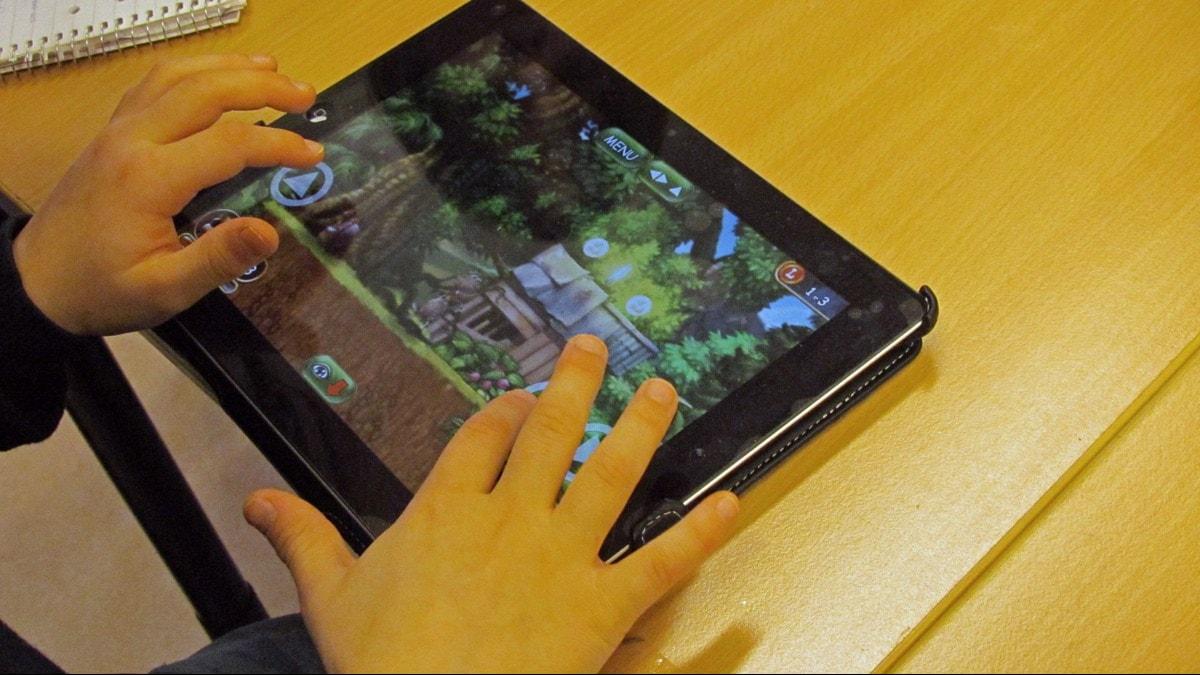 Ett par barnhänder spelar spel på en Ipad. Foto: Leo Vasquez / SR