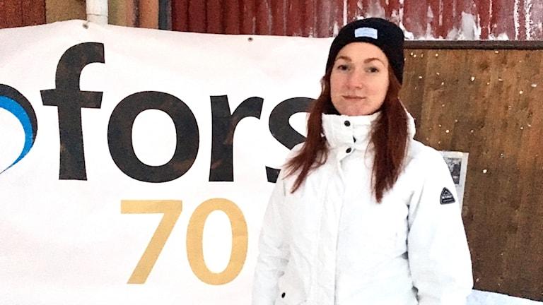 Carolina Näsman framför en skylt med del av texten Kramfors 70 år. Foto: Anton Kårén/Sveriges Radio