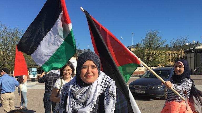 Kvinna omgiven av palestinska flaggor