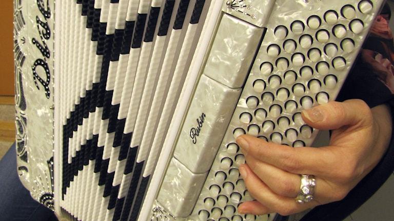 Pärlemorvitt dragspel med en hand på knapparna. Foto: Karin Lönnå/Sveriges Radio