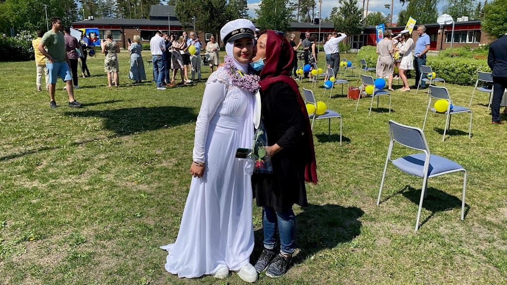 Taiba Abassi står i en fotsida vit klänning med vit spets på axlarna. Hon har vita gymnaskor på fötterna och en vit hijab på sig under studentmössan. Runt halsen hänger en krans med lila syréner. Till höger står hennes mamma Zahra i jeans, svart tröja och en röd sjal om huvudet. Zahra har munskyddet neddragen under hakan och ger dottern en puss på kinden. I bakgrunden syns stolar, ballonger och andra studenter som firas av anhöriga på skolgården vid Timrå Gymnasium.
