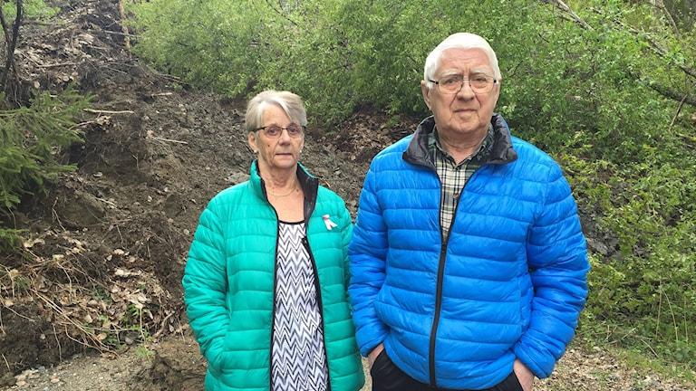 Rose-Marie och Sten-Olov Molin vid kanten av de stora jordmassorna som rasat över vägen. Foto: Viktor Åsberg/Sveriges Radio