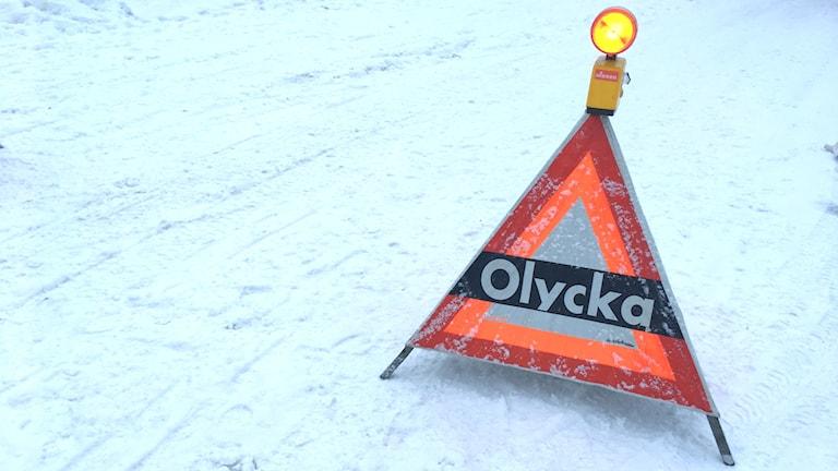 Varningstriangel med texten olycka står på en snötäckt väg.