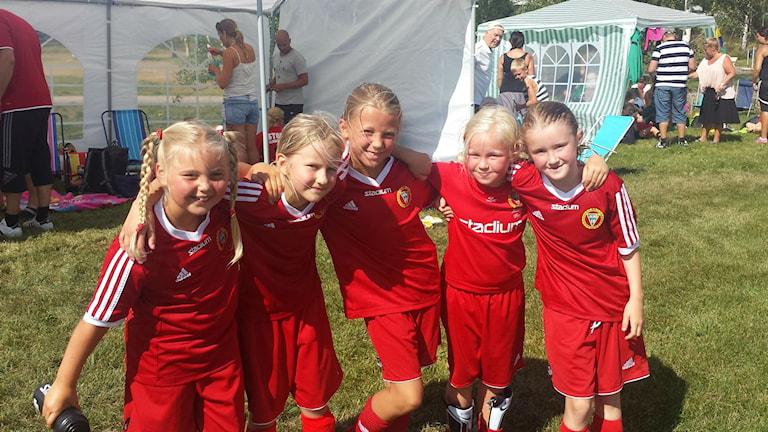 Fem rödklädda fotbollsflickor som håller om varandra och skrattar mot kameran.