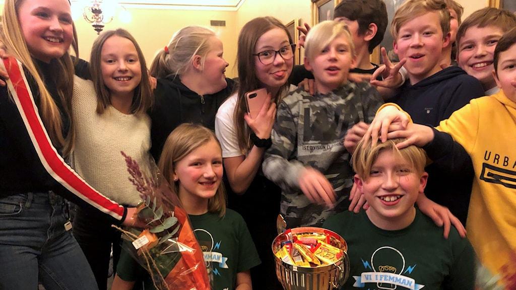 Irma och Hugo i 5A på Högoms skola håller i blommor och segerpokalen omringade av sina klasskompisar. Foto: Niklas Axelsson/Sveriges Radio