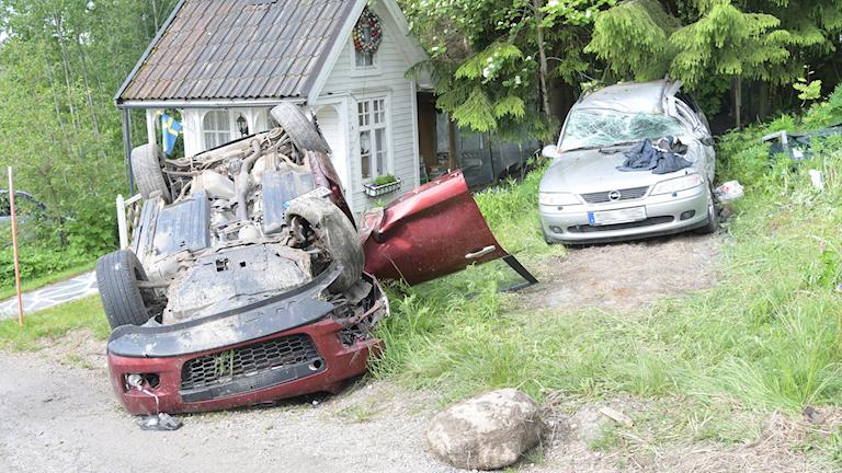 En kraschad bil ligger på taket och bakom ser man en parkerad bil som är skadad och ett litet gårdshus.