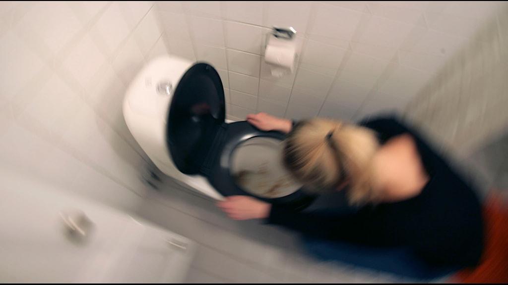 Kvinna har vinterkräksjukan och spyr i en toalettstol. Foto: Fredrik Sandberg/TT