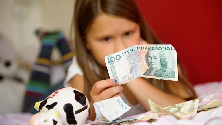 Flicka länsar spargrisen och räknar pengar. Foto:  Henrik Montgomery/TT