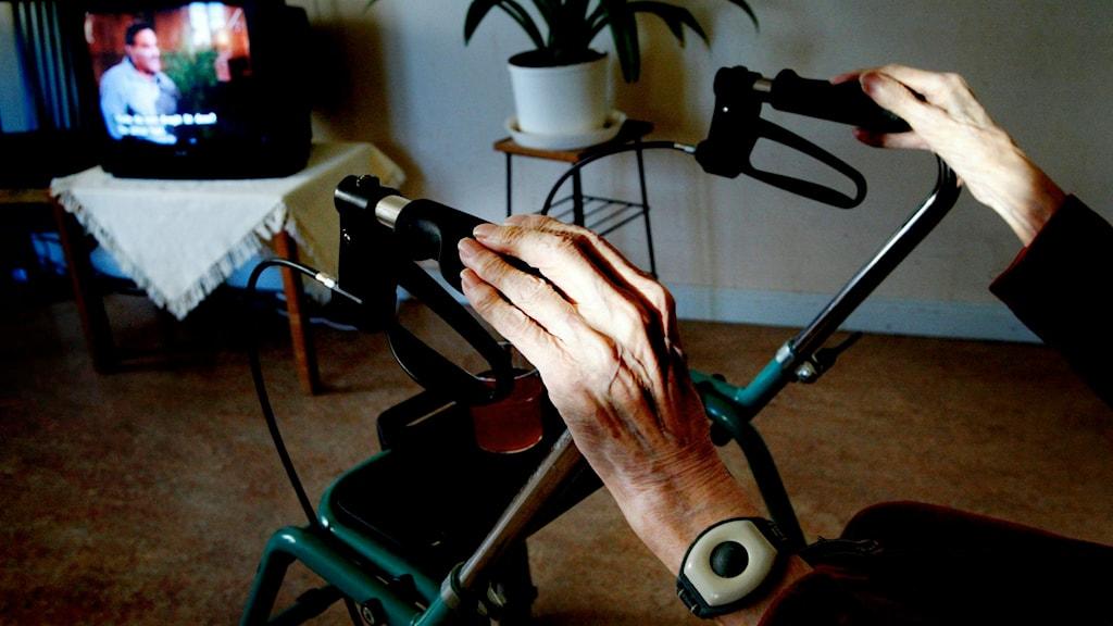 En pensionär vilar händerna på sin rullator när hon tittar på tv. Foto: Jessica Gow/TT
