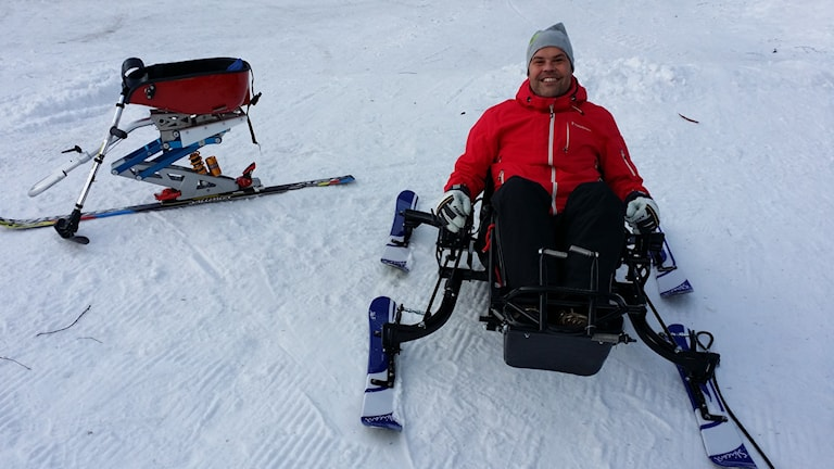 Marcus Söderström visar Sitski (till vänster) och Skicart, två sätt att åka skidor om man är funktionshindrad. Foto: Erik Nyberg/SR