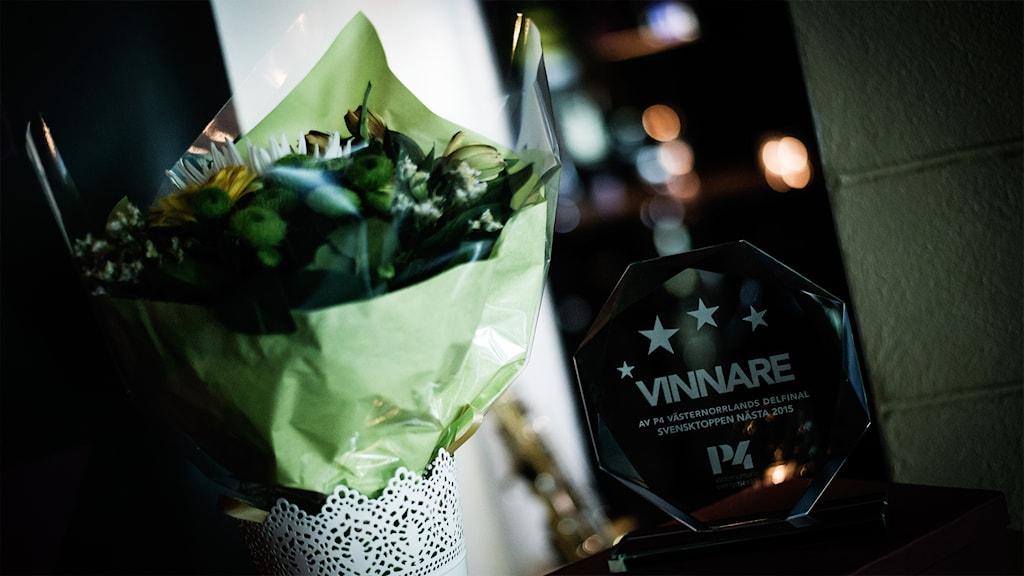 Blommor och segerplakett som väntar på sin vinnare. Foto: Thea Holmqvist/SR