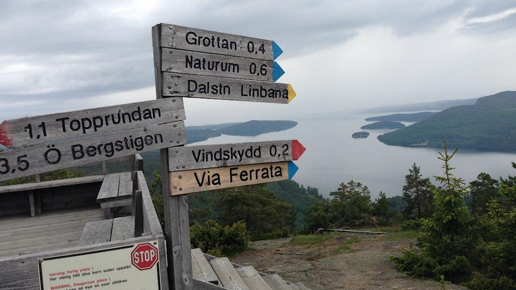 Skyltar som visar riktning och avstånd till olika platser från Skulebergets topp. Foto: Peter Hansson/Sveriges Radio