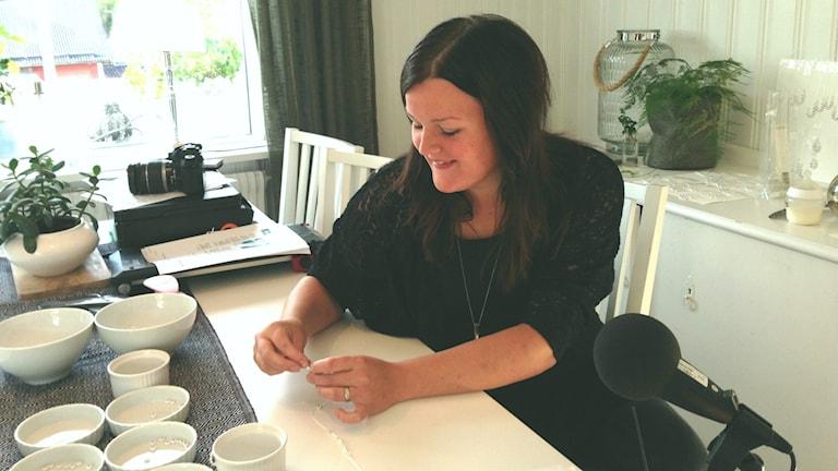 Ida Hamberg trär pärlor på ett snöre hemma vid köksbordet. Foto: Peter Hansson/Sveriges Radio