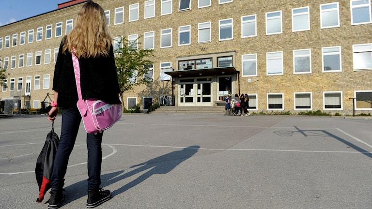 En ensam flicka på väg till skolan över en tom skolgård där en grupp flickor står vid ingången till skolbyggnaden. Foto: Janerik Henriksson/SCANPIX