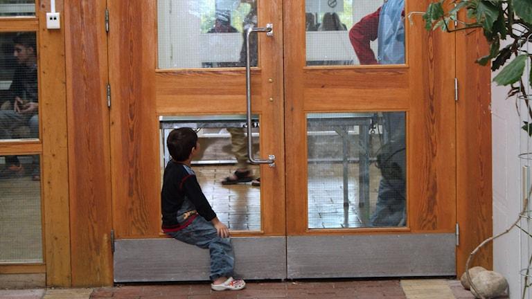 Pojke på asylboende i Helgum sitter i en dörr som saknar ruta. Foto: Sveriges Radio