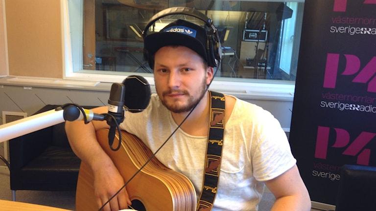Jens Hult i P4-studion, med gitarr på magen. Foto: Karin Lönnå/Sveriges Radio