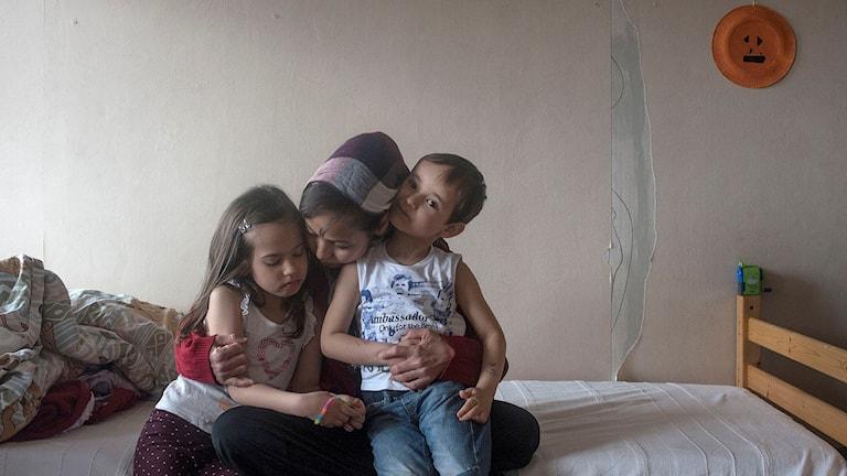 Kvinna och hennes två barn på en obäddad säng. Foto: Linda Maria Thompson. (Bilden är beskuren).