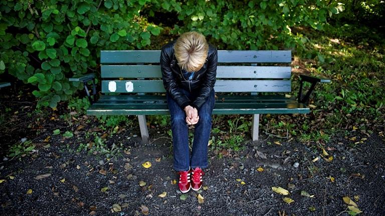 Deprimerad kvinna sitter på en parkbänk. Foto: Jessica Gow/TT