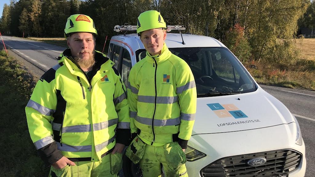 Flaggvakterna Brogge Brohagen och Anton Svedberg står bredvid en bil.