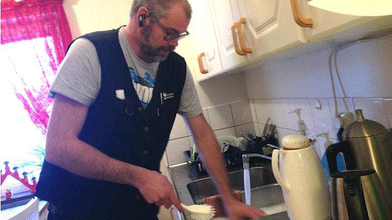 Mikael Schmidt diskar i den marinblå väst som arbetsgivaren tillhandahållit, men med privat, grå t-shirt. Foto: Peter Hansson/Sveriges Radio