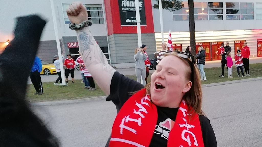 Emma Könberg, ordförande i Timrå IK supporterklubb, lyfter armen i luften i en segergest.