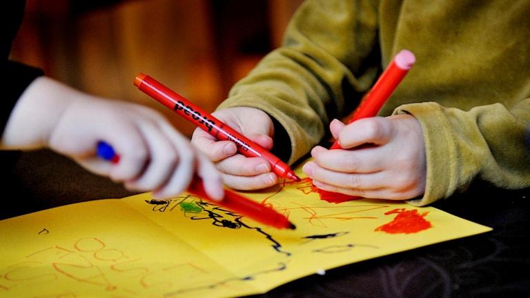 Barn ritar en teckning på dagis på gult papper. Foto: Jurek Holzer/TT