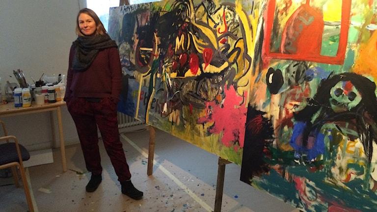 Angelica Frank vid en av de stora målningarna i den öppna verkstaden för flyktingar. Foto Ulla Öhman