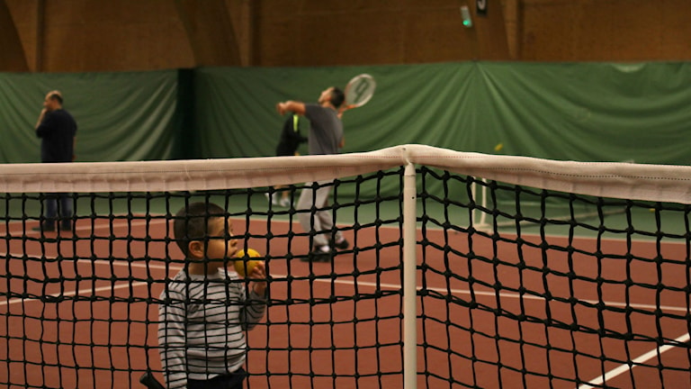 Flyktingar spelar tennis, nät i förgrunden, barn bakom nätet. Foto: Karin Lönnå/Sveriges Radio