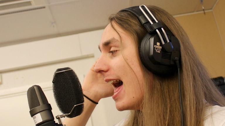 Rasmus Harnesk Wiklund, sångare i gruppen Coming of age, sjunger i mikrofonen. Foto: Karin Lönnå/Sveriges Radio