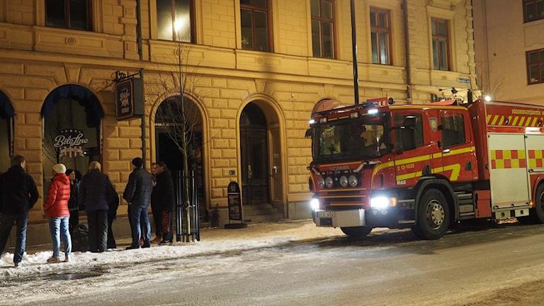 Brandbil på gata och människor på trottoar.