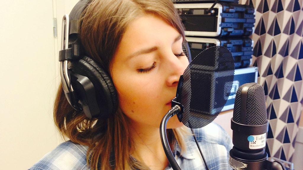 Närbild på när Stina Joza sjunger i studion. Foto: Karin Lönnå/Sveriges Radio