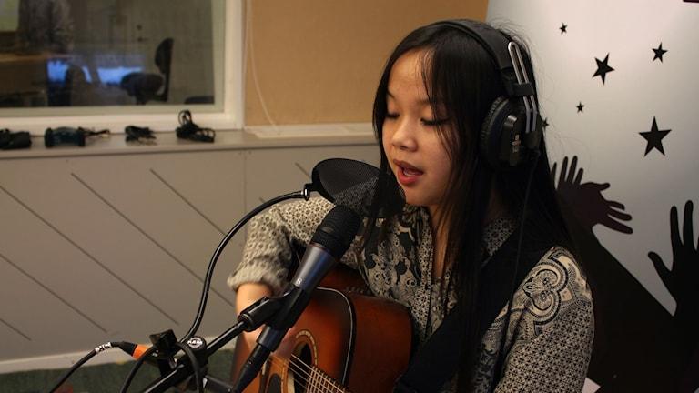 Klara Li Andersson sjunger och spelar i studion. Foto: Karin Lönnå/Sveriges Radio