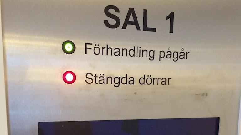 Lamporna tända för att förhandling pågår med stängda dörrar i sal 1. Foto: Pether Öhlén/SR