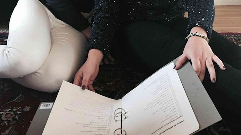 Två tjejer bläddar i en pärm med DISA-metoden. Foto: Sveriges Radio