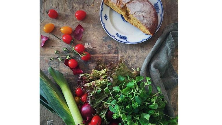 Tomater, purjolök och ett hembakat bröd på ett vackert gammalt träbord. Foto: Christina Sandberg