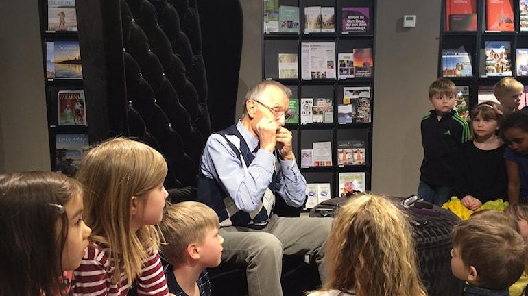 Folke Sandberg spelar munspel för påsklovslediga barn. Foto: Niklas Axelsson/Sveriges Radio