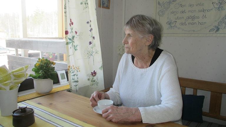 Elsa Brodin med kaffekopp hemma vid köksbordet. Foto: Peter Hansson/Sveriges Radio
