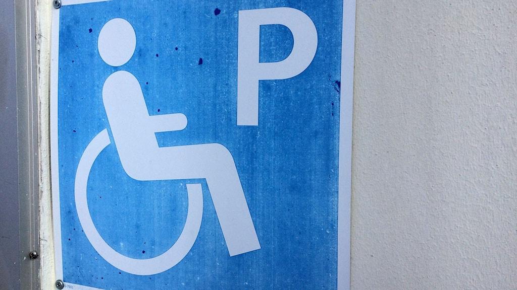Skylt för handikapp-parkering på husvägg. Foto: Ann-Charlotte Carlsson/Sveriges Radio