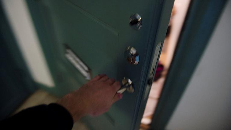 En person öppnar en lägenhetsdörr.